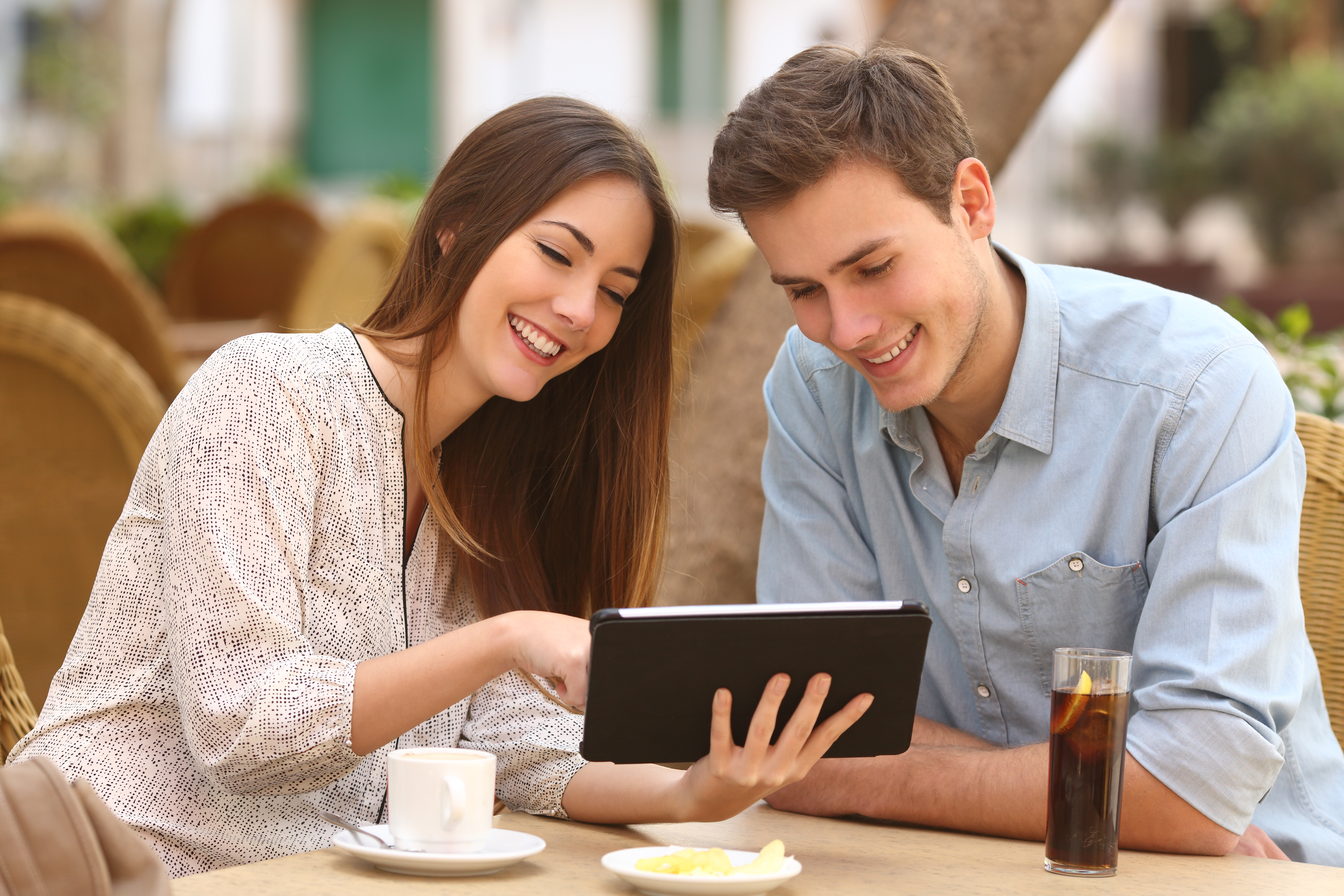 Happy couple watching media in a tablet in a restaurant terrace